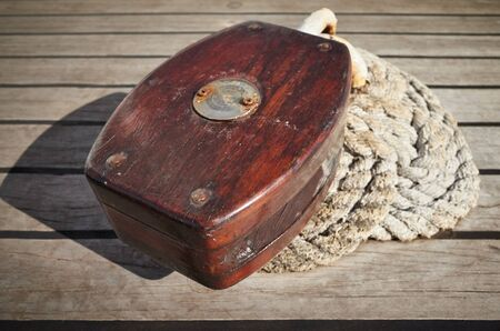 Close up picture of an old wooden pulley block on a deck, selective focus. Stockfoto