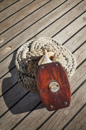 Close up picture of an old wooden pulley block on a deck, selective focus. Foto de archivo