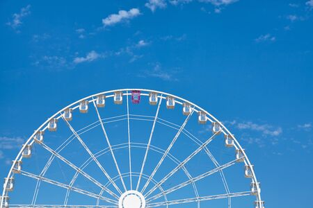 Ferris wheel with one car pink colored against the blue sky.