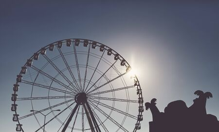 Silhouette of a Ferris wheel at sunset, color toning applied.