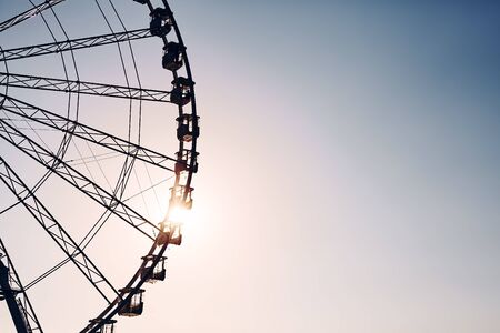 Silhouette of a Ferris wheel at sunset, color toning applied, space for text. Stockfoto