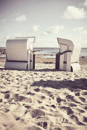 Retro stylized picture of two empty wicker beach chairs on a beach.
