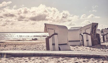 Retro stylized picture of empty wicker beach chairs on a beach at sunset.