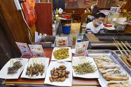 Guilin, China - September 15, 2017: Edible insects on a night market restaurant display.