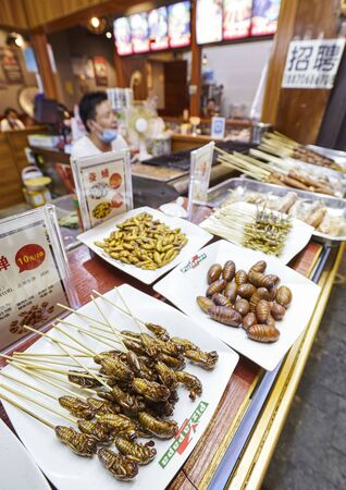 Guilin, China - September 15, 2017: Edible insects on a night market restaurant display, focus on the foreground.