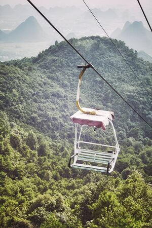 Retro toned picture of an old chairlift in Karst Mountains, Guilin, China. Stockfoto