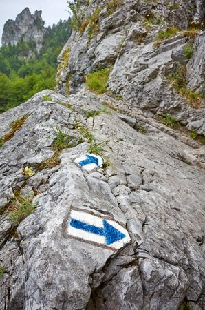 Hiking trail blue paint arrow marking on a rock, selective focus. Stockfoto