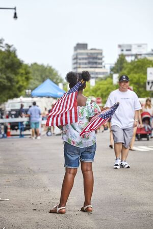 New York, USA - July 04, 2018: Woman with American Flags during federal holiday in the United States commemorating the Declaration of Independence. Redactioneel