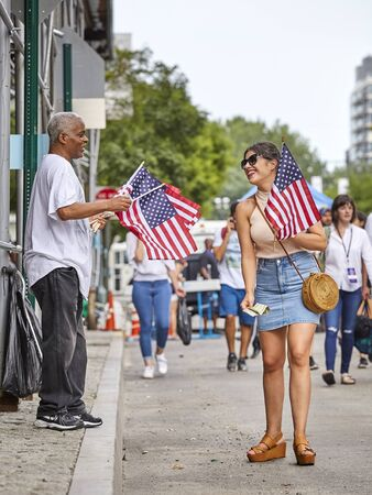 New York, USA - July 04, 2018: Woman buys American Flag during federal holiday in the United States commemorating the Declaration of Independence.