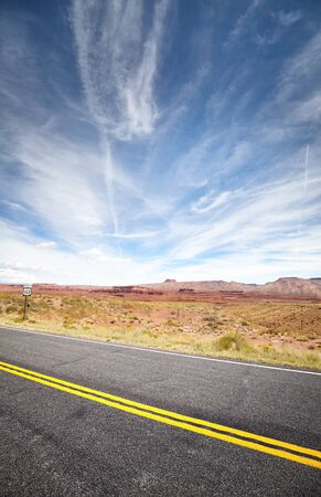 U.S. Highway 163 near Monument Valley, focus on asphalt. The highway is a part of the Trail of the Ancients, a National Scenic Byway and runs in Arizona and Utah, USA.