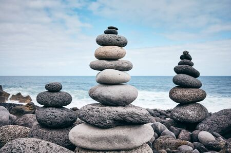 Stone stacks on a beach, balance and harmony concept, color toning applied, selective focus.