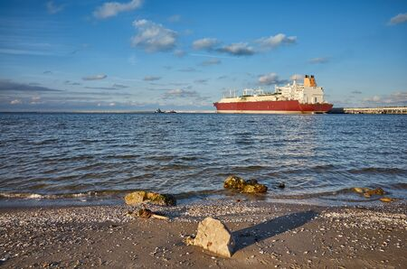 Beach with LNG tanker in distance at sunset in Swinoujscie, Poland. Stock Photo