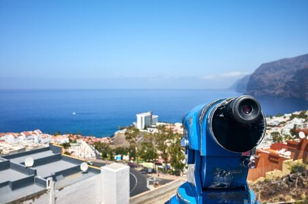 Monocular telescope pointing at Los Gigantes town, selective focus, Tenerife, Spain.
