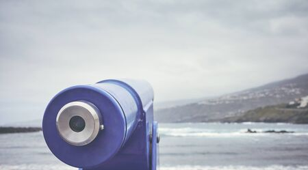 Telescope pointing at the horizon on a beach, selective focus, color toning applied, Tenerife, Spain.