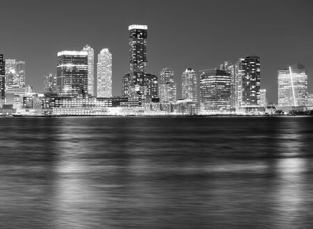 Black and white picture of Jersey City skyline at night, USA.