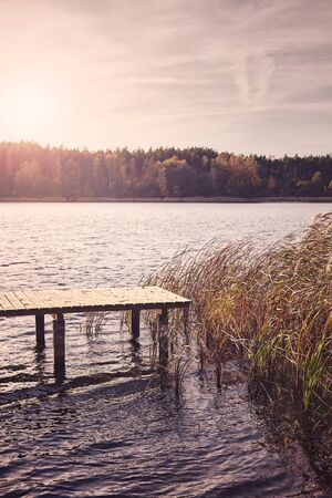Lake with a wooden bridge at sunset, color toning applied.