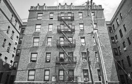 Black and white picture of an old brick building with fire escape, New York, USA. Foto de archivo
