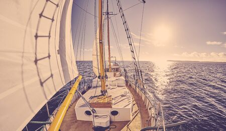 Old sailing ship at sunset, color toning applied.