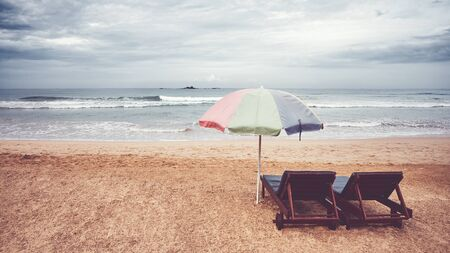 Two sunbeds and umbrella on an empty beach, color toning applied, Sri Lanka. Stock Photo