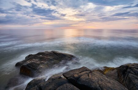 Scenic sunset over water seen from rocky shore, long time exposure, Sri Lanka West Coast. Stock Photo