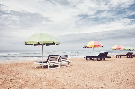 Sunbeds with umbrellas on an empty beach, color toning applied, Sri Lanka.