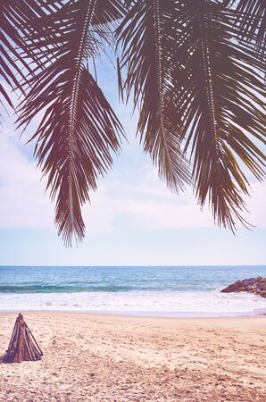 Tropical beach with palm leaves, summer vacation concept, color toning applied, Sri Lanka.