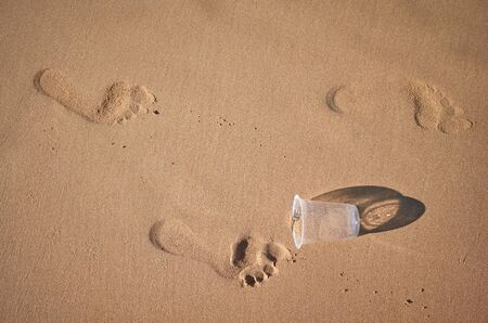 Footprints and plastic cup on a sandy beach, conceptual picture. Stock Photo