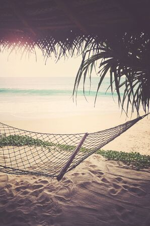 Tropical beach with hammock, summer getaway concept, retro color toning applied.