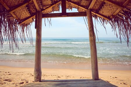 Tropical beach wooden shade, color toning applied, summer vacation concept. Stock fotó
