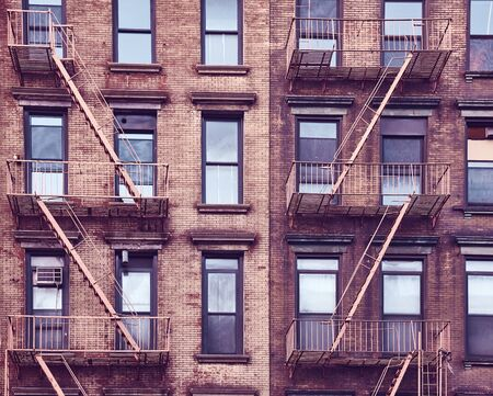 Vintage toned photo of a residential building with fire escapes, Manhattan, New York City, USA.