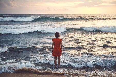 Rear view of a woman in orange dress standing still in the rough ocean at sunset, color toning applied.