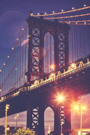 Manhattan Bridge with lens flares seen from Brooklyn at dusk, color toned picture, New York, USA. Stock Photo