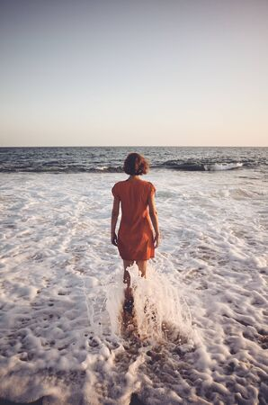 Rear view of a woman standing still in the ocean at sunset, color toning applied. Stock Photo