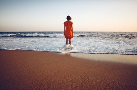 Rear view of a woman in orange dress standing still in the sea at sunset, color toning applied.