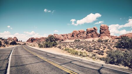 Retro colors toned picture of a scenic road in Arches National Park, Utah, USA.