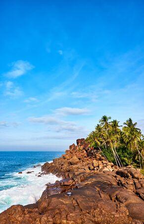 Rocky shore of the Indian Ocean in Unawatuna on a sunny day, Sri Lanka. Stock Photo