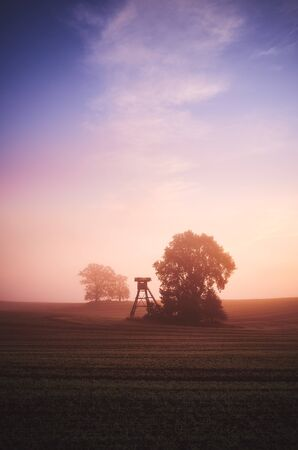 Rural landscape with silhouette of hunting tower on a field at sunrise. Stock Photo