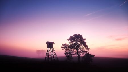 Rural landscape with silhouette of an observation or hunting tower on a field at dawn. Stock Photo