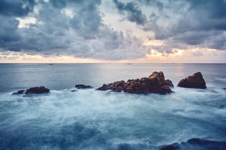 Rocky coast at sunset, color toned long exposure picture, Sri Lanka.