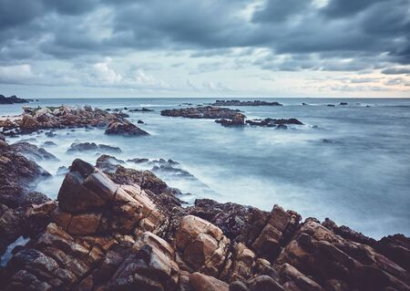 Rocky beach at sunset, color toned long exposure picture, Sri Lanka. Stock Photo