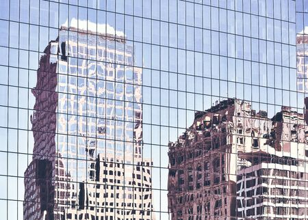 New York old buildings reflected in windows of a modern skyscraper, color toned urban background. 免版税图像