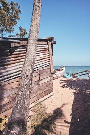 Retro toned picture of an old fishing shack by a beach.