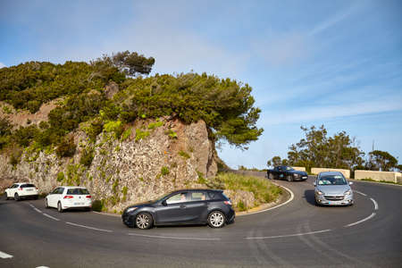 Tenerife, Spain - April 29, 2019: Cars on a scenic road bend in Anaga mountain range, one of the top tourist attractions on the island.