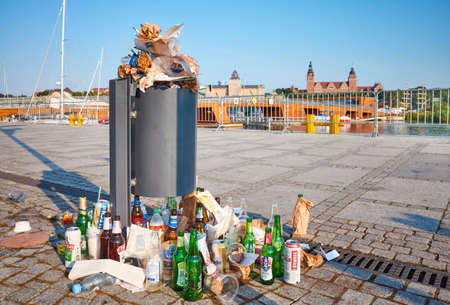 Szczecin, Poland - July 19, 2020: Morning view of an overflowing trash can on the pavement of Lasztownia Island boulevard with garbage sitting on the ground after night party.