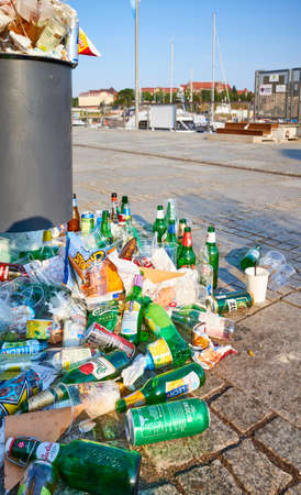 Szczecin, Poland - July 19, 2020: An overflowing trash can on the pavement of Lasztownia Island boulevard at sunrise, with garbage sitting on the ground after night party. 新闻类图片
