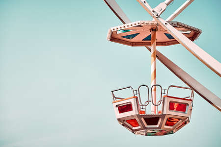 Close up picture of Ferris wheel car with cloudless sky in background, color toning applied, space for text.