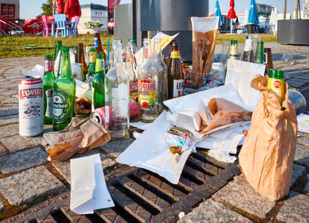 Szczecin, Poland - July 19, 2020: Close up picture of beer bottles and garbage left on the pavement of Lasztownia Island boulevard, selective focus. 新闻类图片
