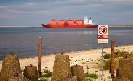 Swinoujscie, Poland - August 21, 2020: No entry sign at closed protection zone by LNG Terminal in Swinoujscie with tanker in distance at sunset.
