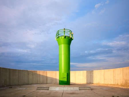 Green lighthouse surrounded by a concrete wall at sunset. Standard-Bild