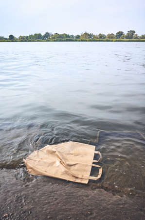 Discarded shopping paper bag in water, environmental pollution concept picture.